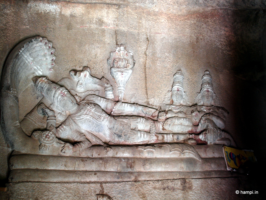 Lord Vishnu rests on the cosmic serpent . Vishnu's consorts siting near his feet. Note, Lord Brahma sitting on the lotus that sprouted from Vishnu's naval.