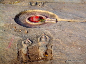 Linga with vermilion applied as mark of reverence. Also seen are images of people worshiping the Linga. Image from the Riverside Ruins site.