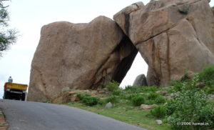 Sister Boulders, locally called the 'Akka-Tangi Gudda'.   Once this formed a natural archway on the path to Hampi.   The photograph was taken before this leaning boulders collapsed. Note the faultline visible on the right boulder.  You can see this on the way to the Hampi village from Kamalapura. Located just after the junction where the diversion to the Underground Shiva Temple and Noble Men's Quarters are located.